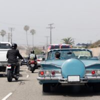 A traffic jam in Malibu, California with a vintage convertible car, motorcycle and pick up truck in summer time