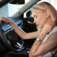Beautiful blond haired woman rubbing her aching neck, sitting in her car. Female driver rubbing her neck, tired from driving